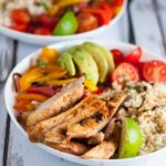 Chicken Fajita Bowl with Cauliflower Rice. A paleo meal -in-a-bowl. Succulent fajita chicken, peppers, tomatoes, avocado and cilantro-lime cauliflower rice, all in one bowl, makes a tasty Tex-Mex dinner.
