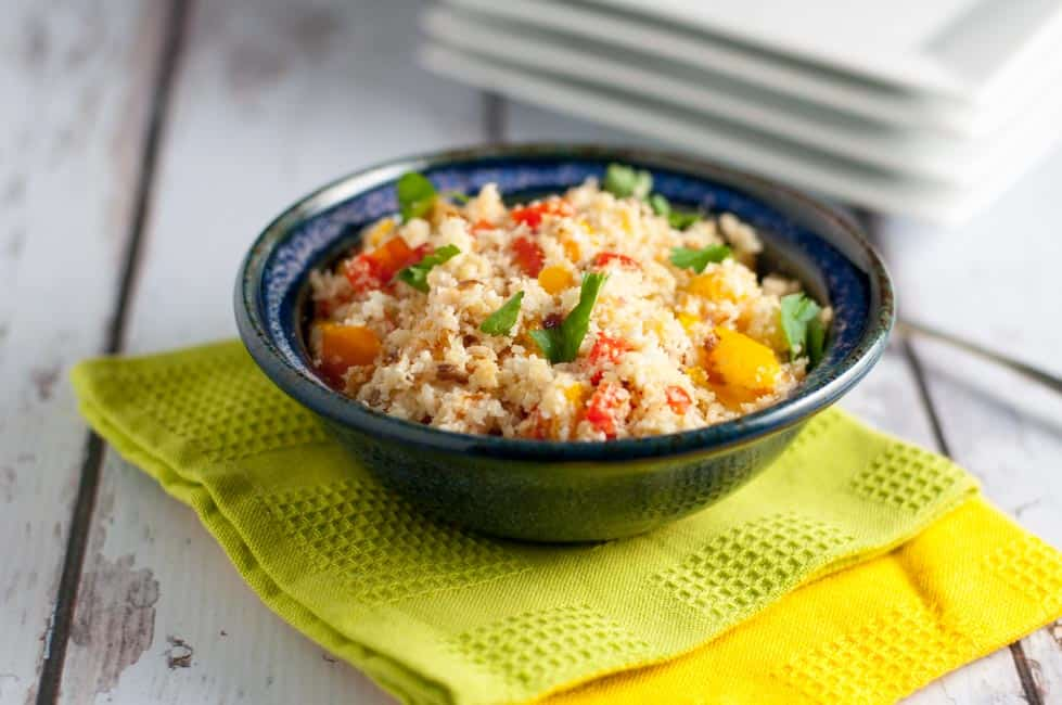 3 Easy Steps to Make Cauliflower Rice. Cauliflower rice with veggies in a blue pottery bowl.