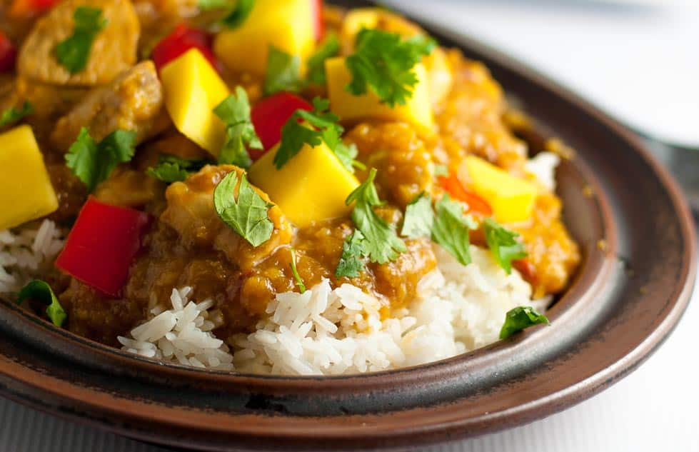 Slow Cooker Thai Mango Chicken with cubed mango and red peppers on coconut rice.