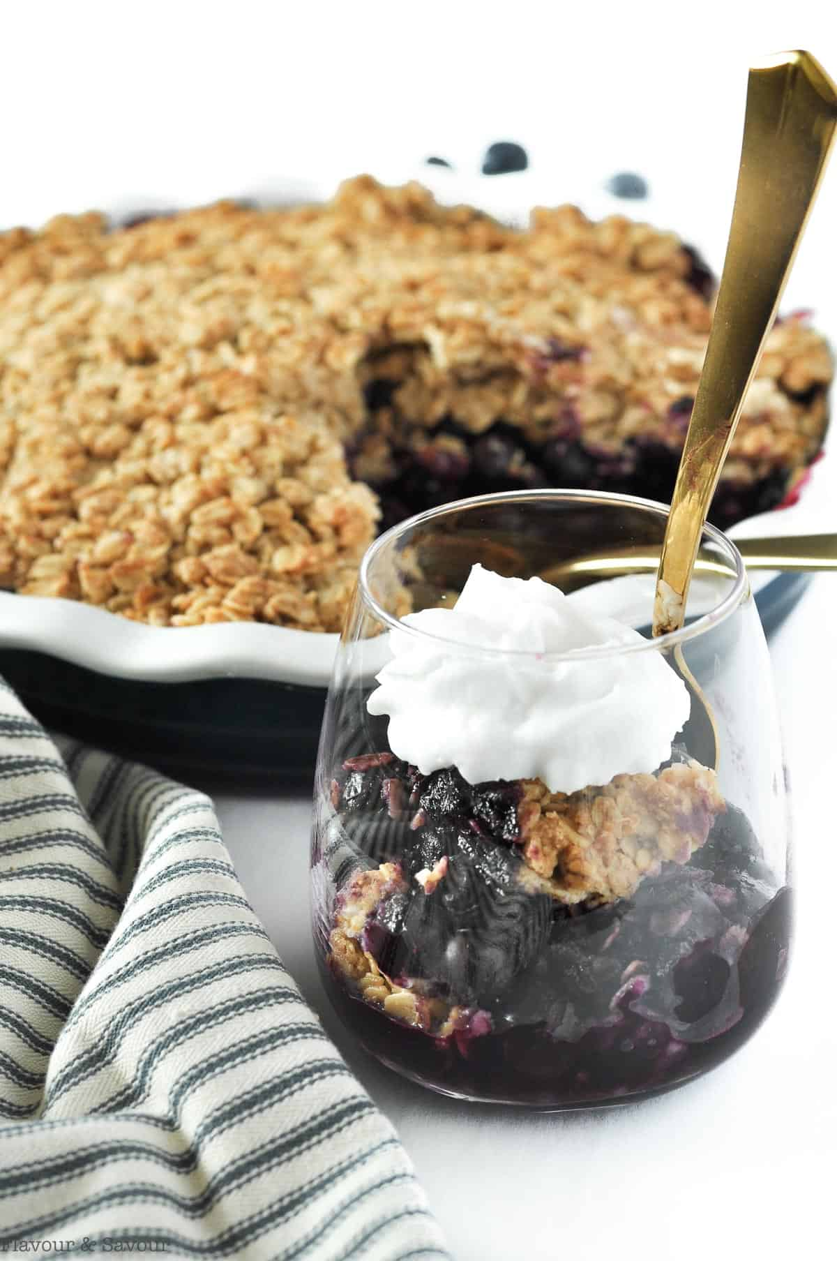 Blueberry Crisp in a dessert glass with a baking dish in the background