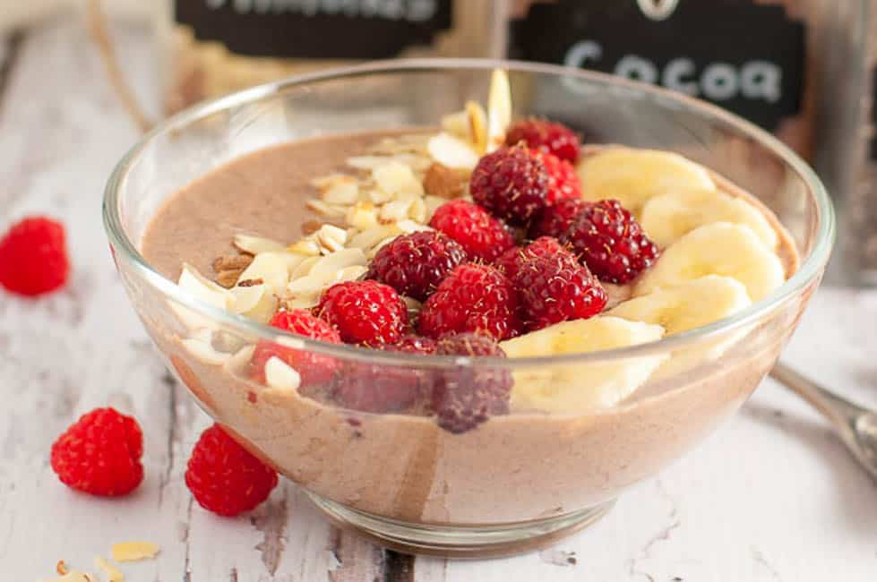 How to Make a Smoothie Bowl garnished with raspberries, bananas and flaked almonds.