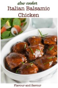 Slow Cooker Italian Balsamic Chicken in a bowl with a green salad and a glass of water