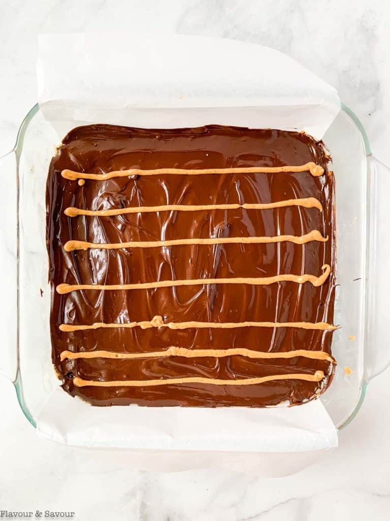 Adding lines of peanut butter to chocolate topping