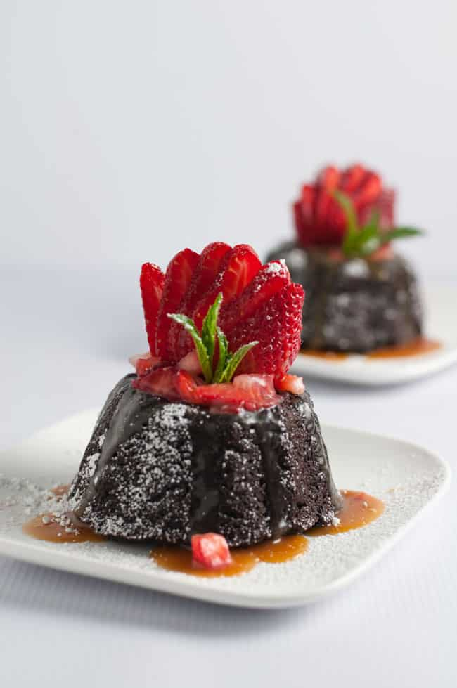 Chocolate Quinoa Mini Bundt Cakes with fresh Strawberries and Caramel Sauce garnished with a fan of fresh strawberries.