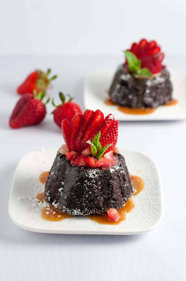 Chocolate Quinoa Mini Bundt Cakes with Strawberries and Caramel, garnished with a fresh strawberry fan.