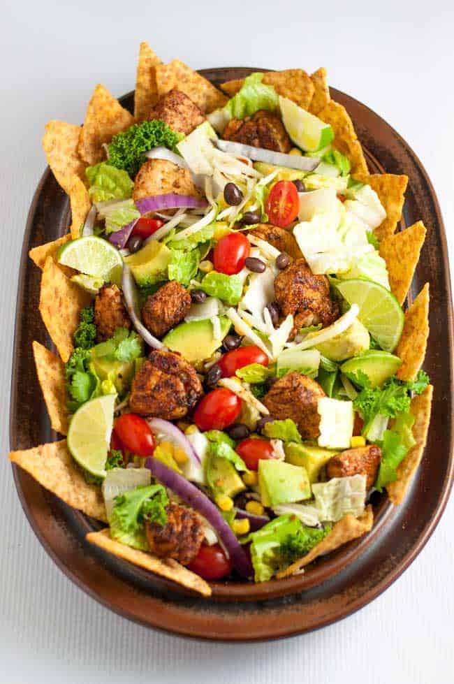Skinny Chopped Chicken Taco Salad. Lean taco seasoned chicken breast cubes, crispy romaine, black beans, corn, tomatoes, red onions, creamy avocados and Monterey Jack cheese, tossed with a lime vinaigrette and served with taco chips. |www.flavourandsavour.com