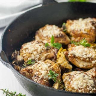 Baked Sun-dried Tomato and Artichoke Chicken thighs in cast iron skillet.