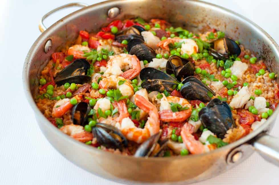 How to host a Paella Party in your kitchen. Tips for making paella, a traditional Spanish rice and seafood dish. Step-by-step instructions for a successful paella party!