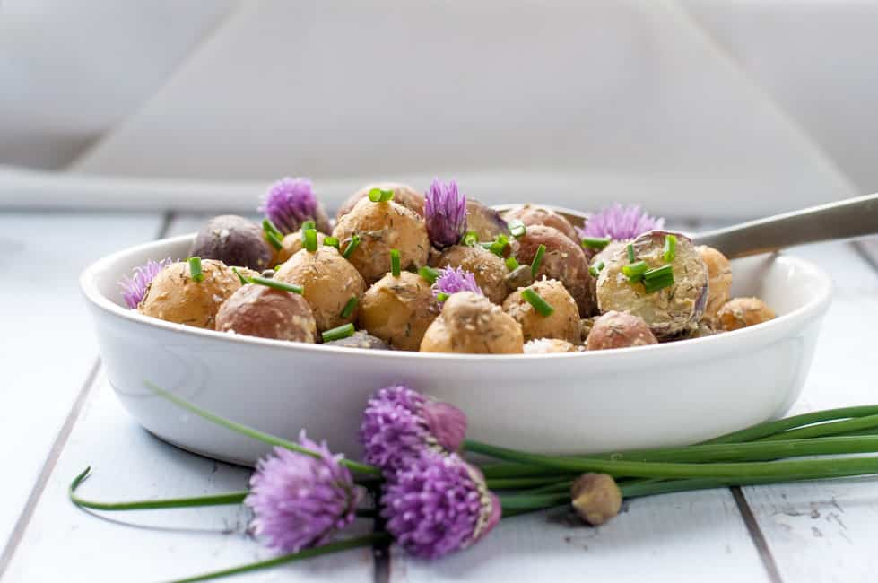 Springtime Potato Salad with Lemon Tahini Dressing in a white oval bowl with purple chive flowers.