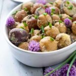 Springtime Potato Salad with Lemon Tahini Dressing in an oval bowl with chive flowers.