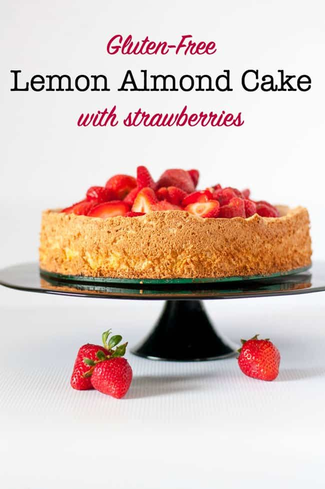 Gluten-Free Lemon Almond Cake with Strawberries on a black pedestal cake stand