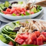 Pouring dressing on Skinny Greek Chicken Bowl with Watermelon and Feta