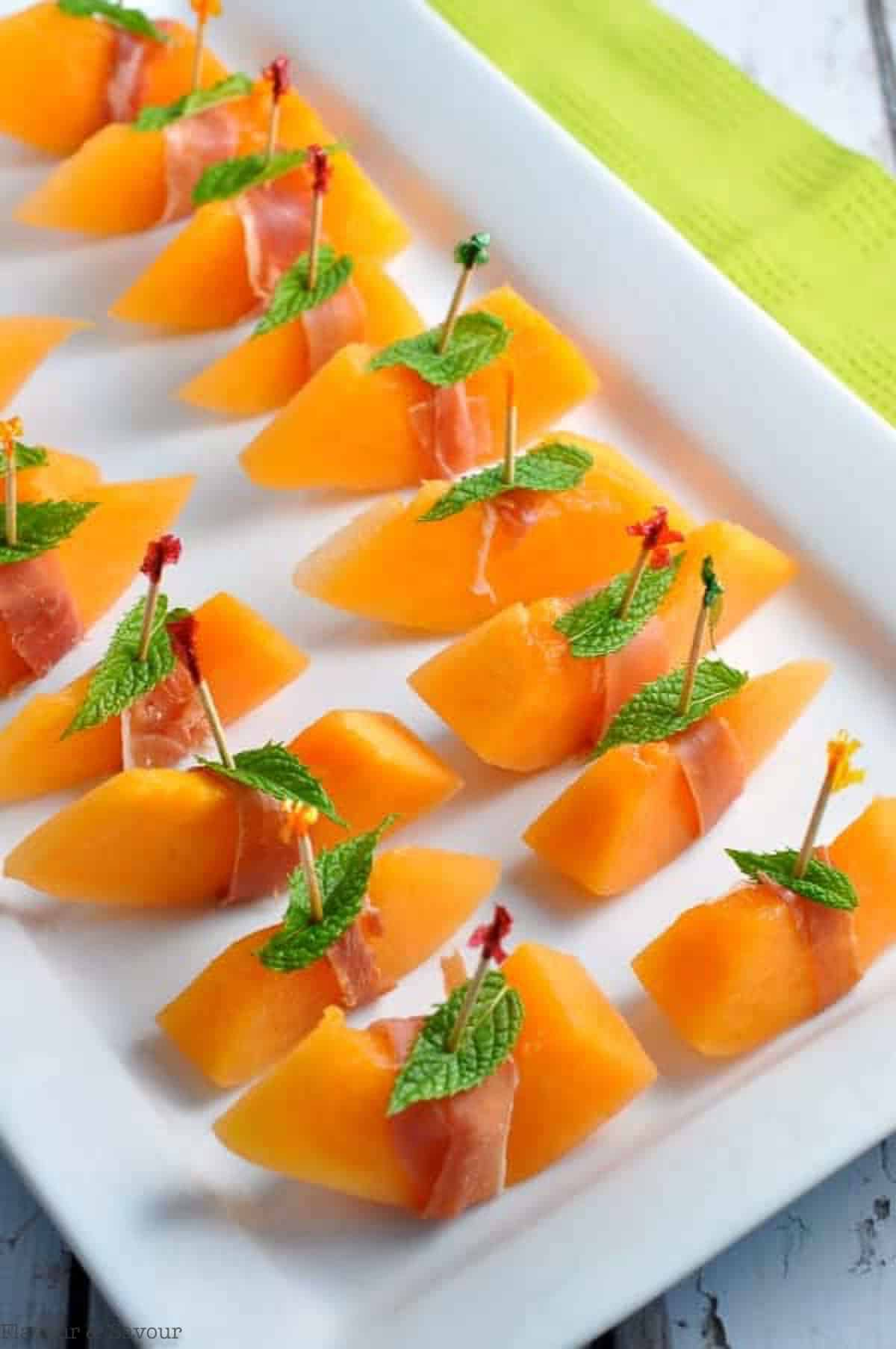 a tray of skewered melon wrapped with prosciutto