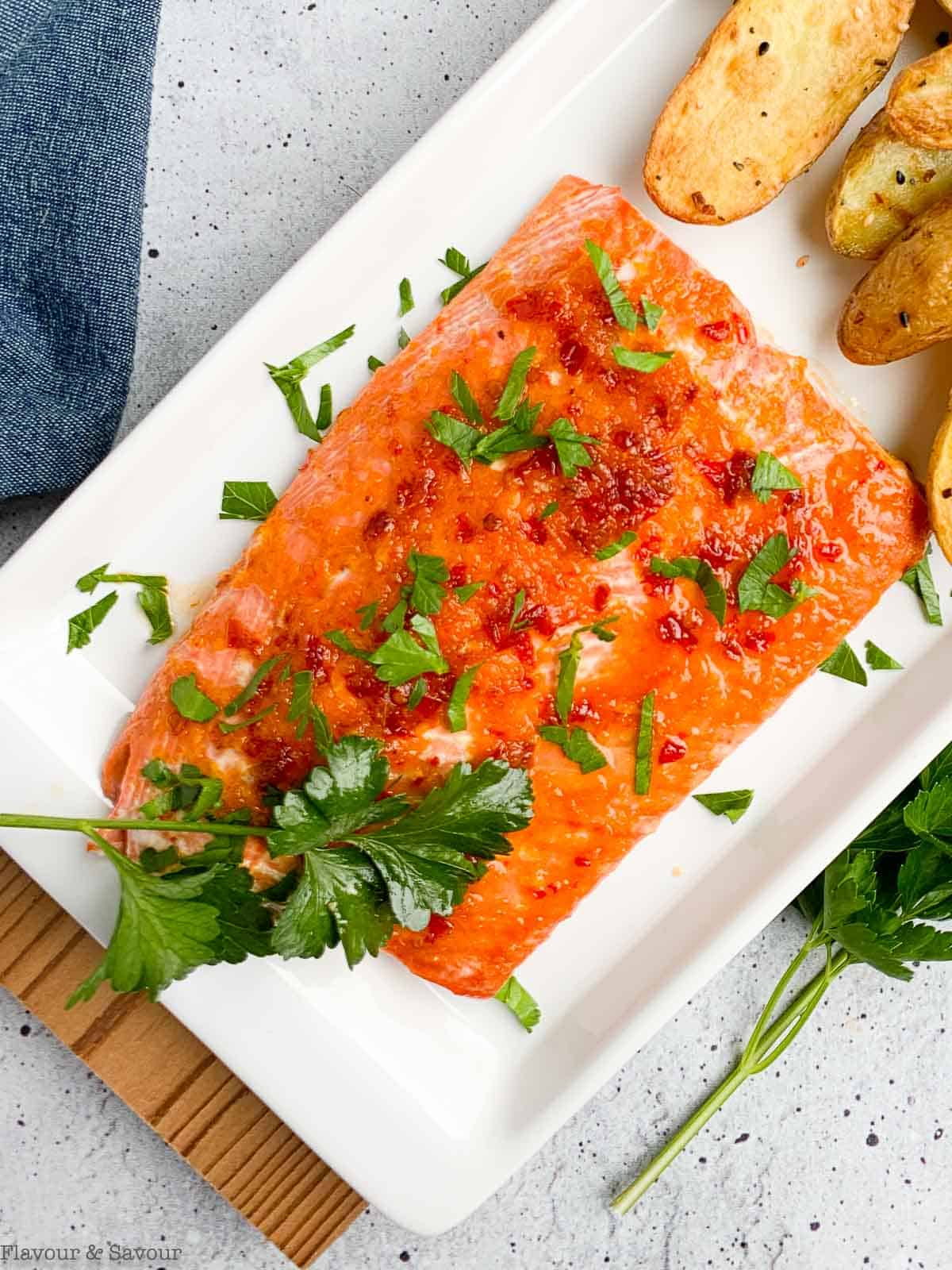 Close up view of Citrus Chardonnay Glazed Salmon on a platter with parsley