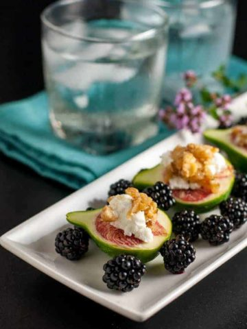 A tray of fresh figs with goat cheese and maple walnuts served with fresh blackberries.