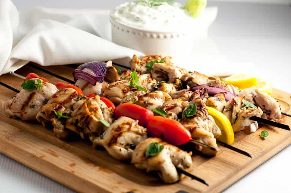 Easy Greek Lemon Chicken Kabobs with Tzatziki Sauce, on a wooden board.