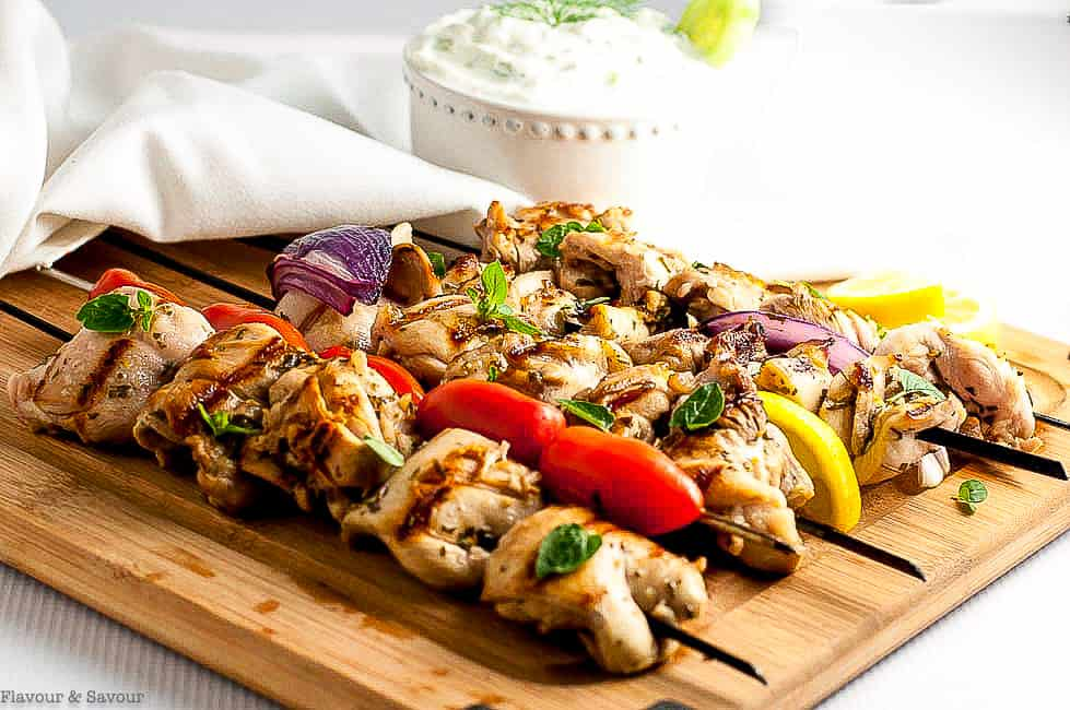Greek Lemon Chicken Kabobs on skewers on a cutting board with a bowl of Tzatziki sauce