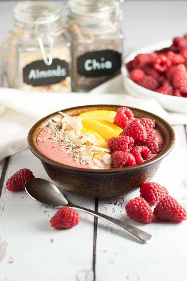 Healthy Peach Melba Breakfast Smoothie Bowl with fresh raspberries
