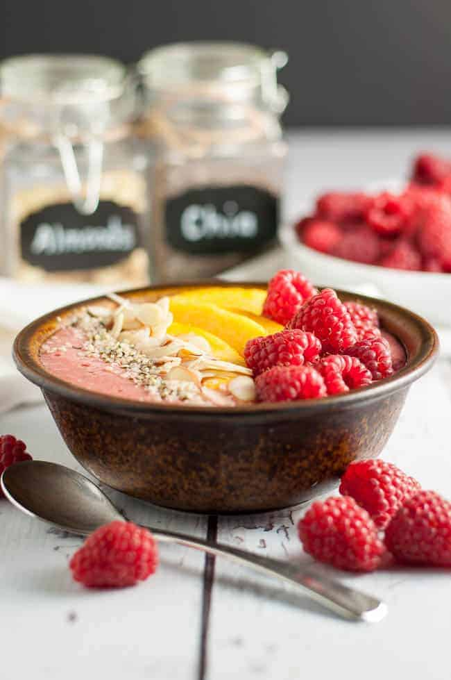 Healthy Peach Melba Breakfast Smoothie Bowl garnished with peaches, raspberries, sliced almonds and hemp seeds.
