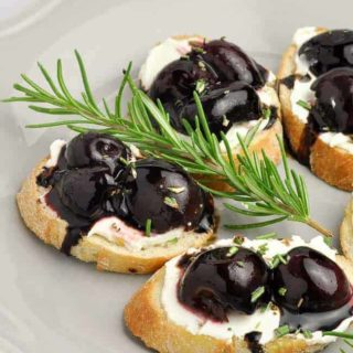 Roasted Cherry Whipped Goat Cheese Crostini appetizers on a plate with a sprig of rosemary