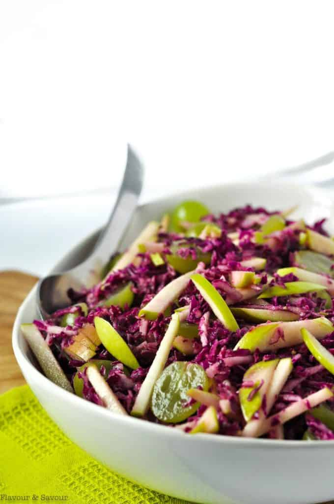 Side view of Grape Apple and Red Cabbage Slaw in a white bowl on a green cloth