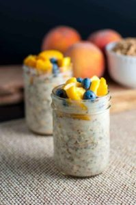 Peach and Blueberry Overnight Oats in 8 oz. Mason jars with fresh peaches in the background.