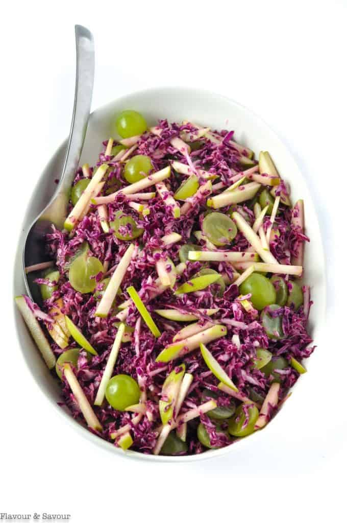 An oval bowl with Grape Apple and ?Red Cabbage Slaw