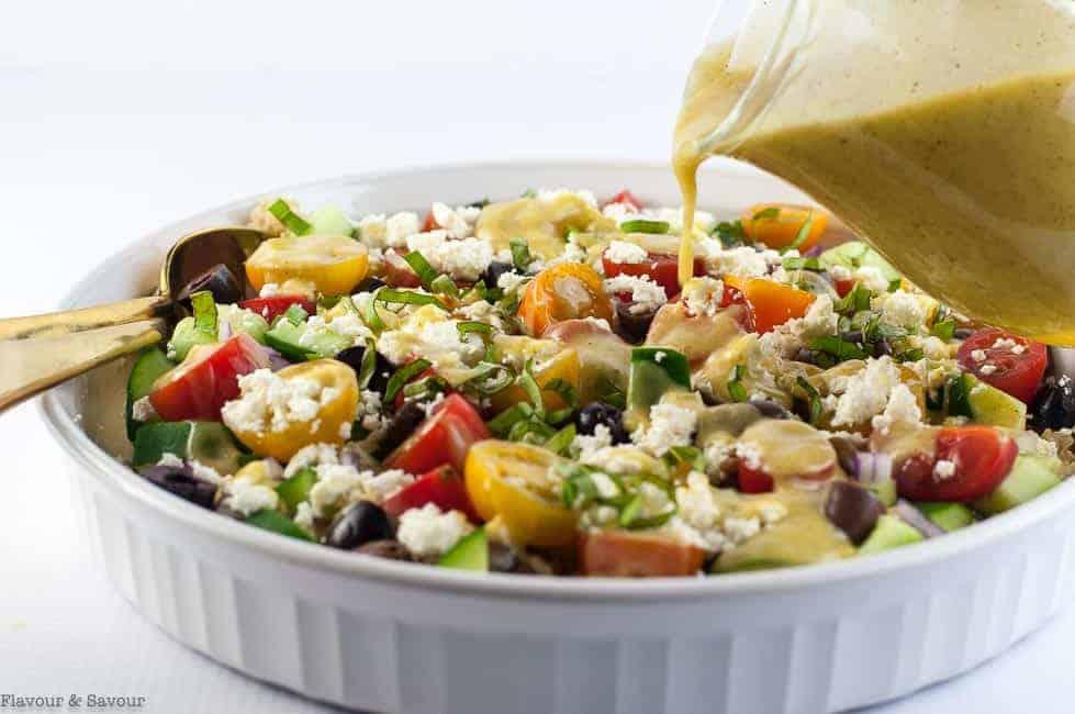 adding dressing to Mediterranean Quinoa Salad