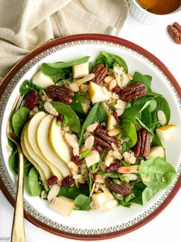 Overhead image of Harvest Quinoa Salad with Cranberries and Pears on a red rimmed plate
