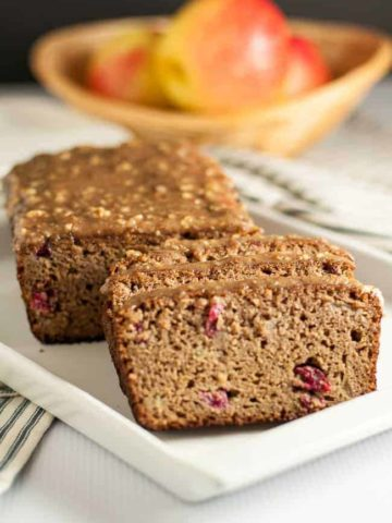 This Paleo Apple Cranberry Bread is tender and moist. It's topped with a naturally sweet glaze made from pecans, maple syrup and coconut oil. A healthy coffee-time snack! |www.flavourandsavour.com