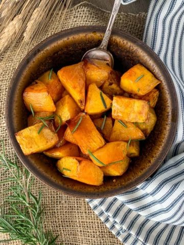 Overhead view of a brown stoneware bowl filled with roasted butternut squash.