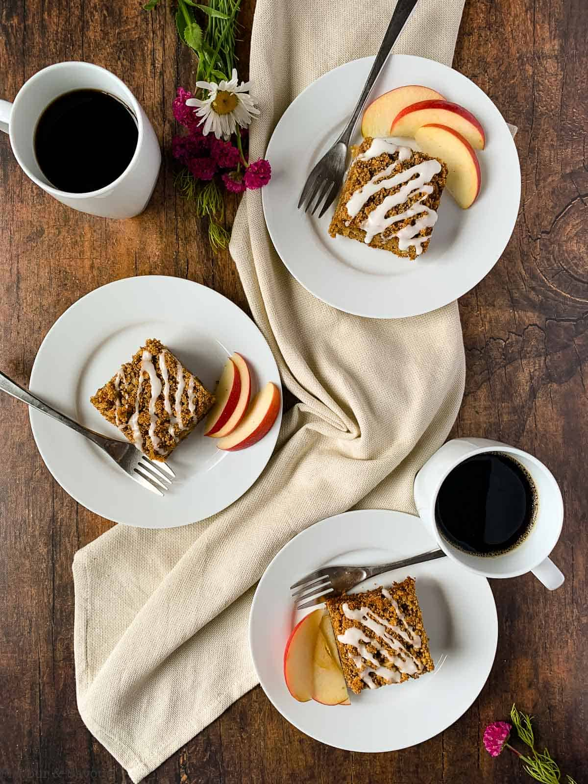 Overhead view of 3 plates of gluten-free apple cinnamon coffee cake with coffee
