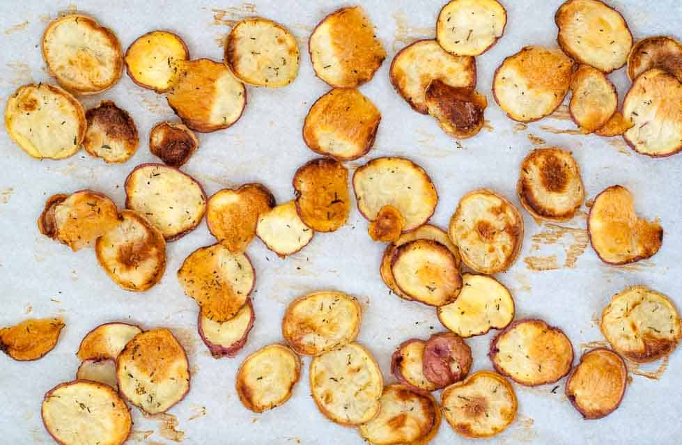 Roasted Potato slices on a baking sheet for Dijon Green Beans with Crispy Potato Chips.