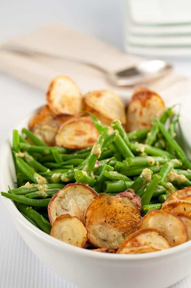Here's a side dish that's an updated version of the old favourite green bean casserole! Tender green beans tossed with a Dijon-shallot vinaigrette and served with homemade crispy potato chips! Just one of Flavour and Savour's collection of gluten free holiday side dishes.|www.flavourandsavour.com