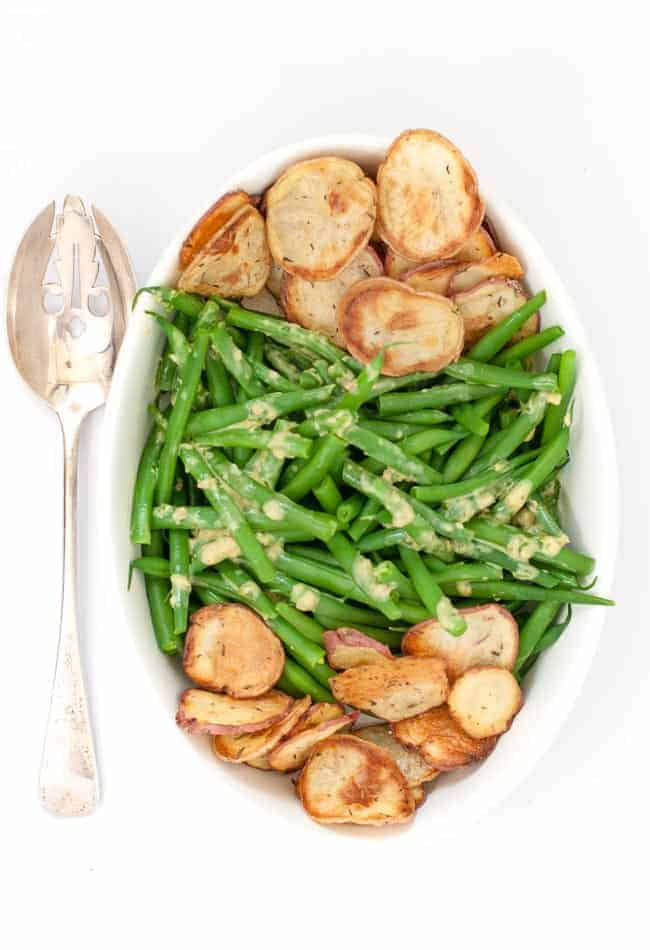 Dijon Green Beans with Crispy Potato Chips in a bowl with a serving spoon