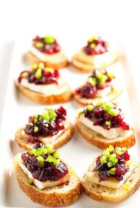These Cranberry Jalapeño Brie Crostini Appetizers add a festive touch to your party and they're a great way to use leftover cranberry sauce! |www.flavourandsavour.com