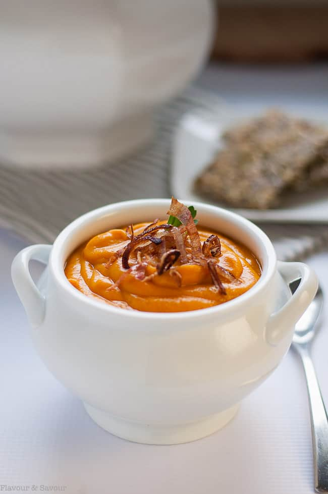 Slow Cooker Sweet Potato Turmeric Soup is a white soup bowl garnished with fried shallots.