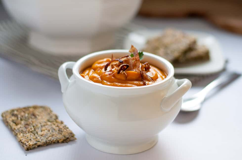 Slow Cooker Sweet Potato Turmeric Soup in a small soup tureen with Super Seedy Snack Crackers