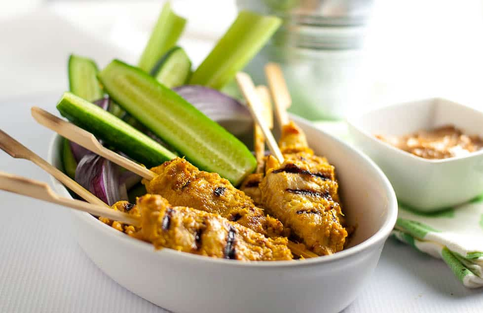 5 skewers of chicken satay with cucumber spears and red onion with a small bowl of peanut sauc.e