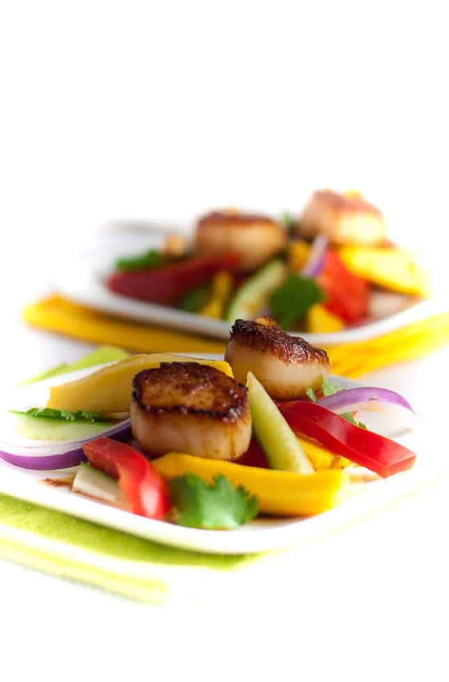 Seared Scallops with Mango Salad. Discover three simple steps to create perfectly seared scallops, and serve them on a colourful salad made with thinly sliced mango, red pepper, cucumber and red onion.