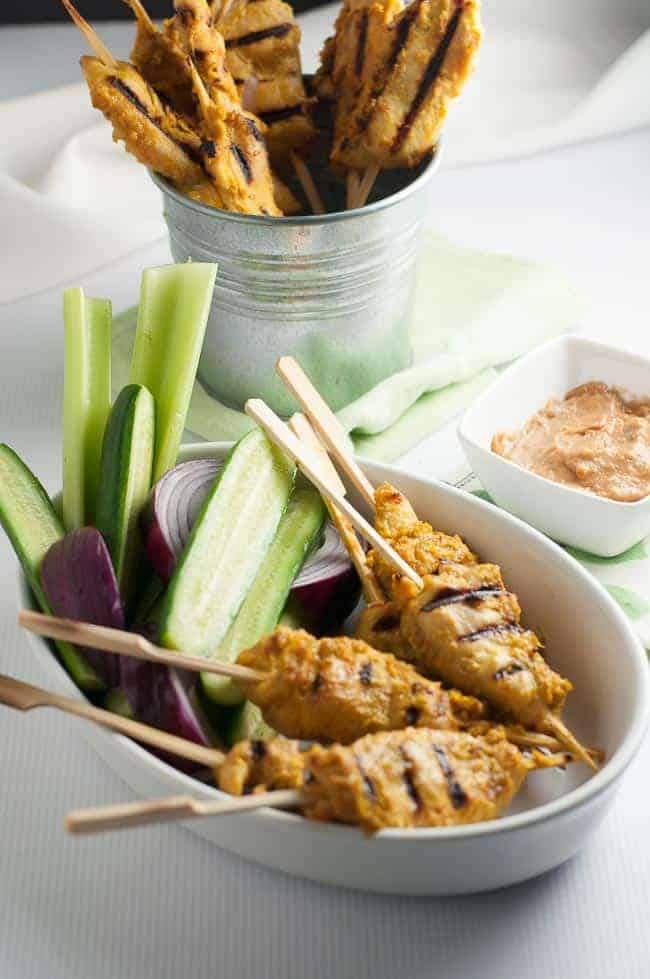 Skewers of chicken satay with cucumber spears, red onion and a small bowl of peanut sauce.