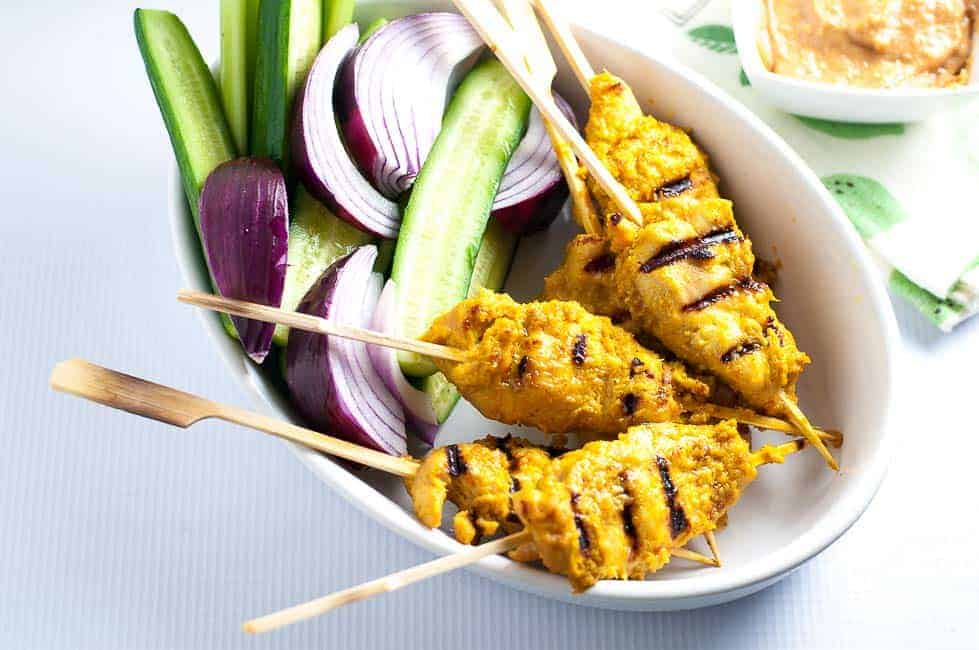 An oval bowl with skewered chicken satay, red onions and cucumber spears.