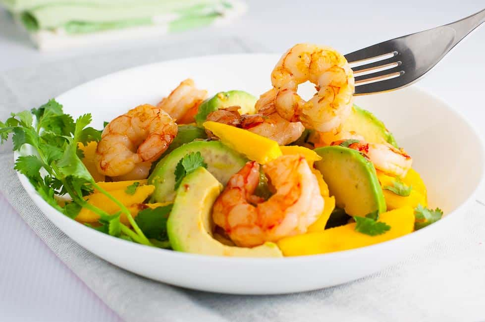 Prawn Mango Avocado Salad with Lemon Lime Dressing in a bowl with a fork spearing a shrimp.