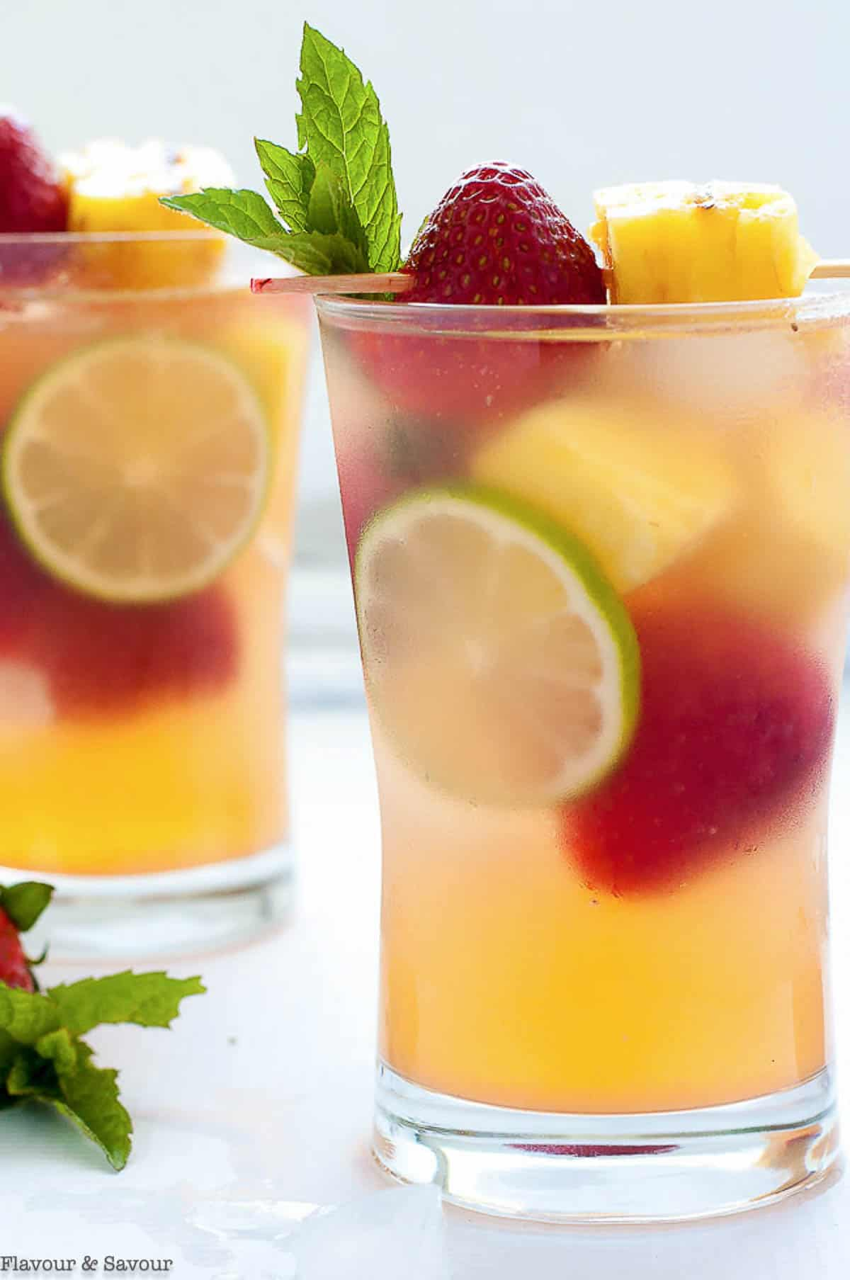 Grilled Pineapple Strawberry Sangria in two glasses with strawberries and lime slices.