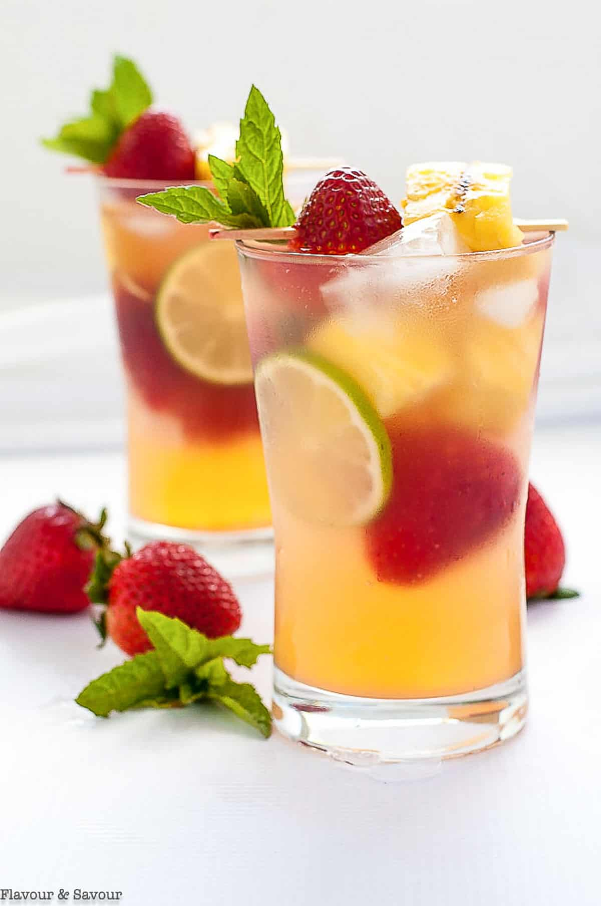 tall glasses of pineapple sangria with strawberries and lime