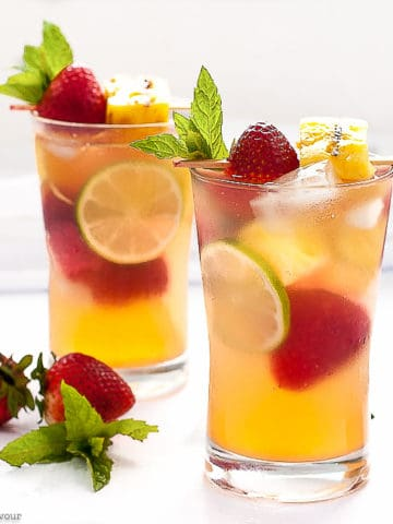Two glasses of Grilled Pineapple Strawberry Sangria with lime slices, strawberries, pineapple and mint leaves