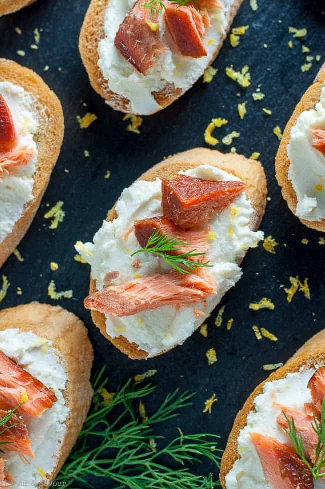 Smoked Salmon Crostini with Whipped Honey Lemon Goat Cheese on a slate tray