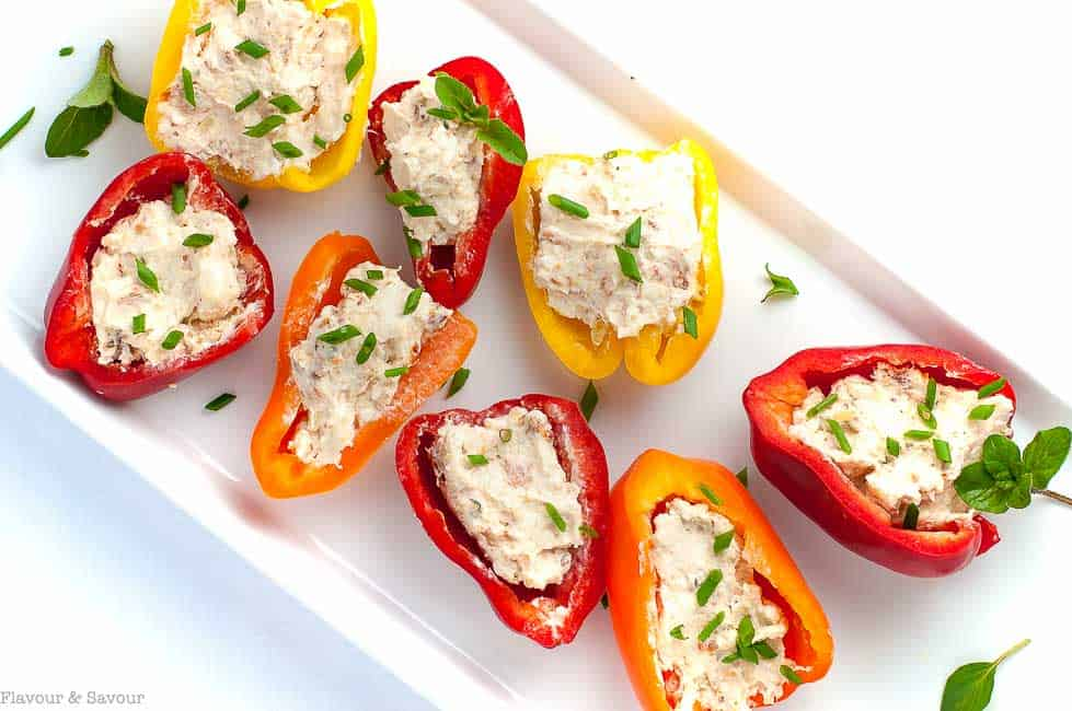\ Sun-dried Tomato, Artichoke and Cheese Stuffed Mini Peppers on a white platter.
