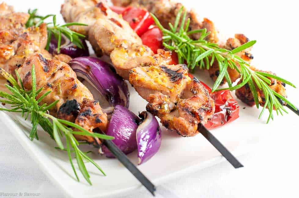 Grilled Rosemary Mustard Chicken Kabobs with skewered red onion and tomatoes with rosemary sprigs.