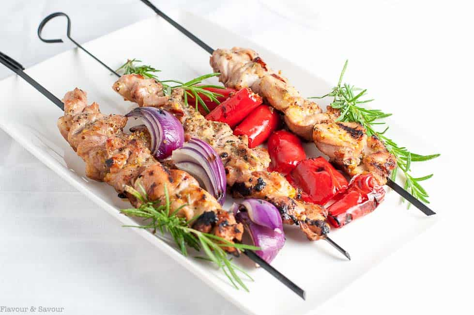 Grilled Rosemary Mustard Chicken Kabobs with skewers of red onion and tomatoes and fresh rosemary.